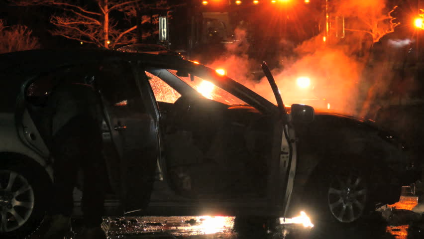 Car accident at night, smoking wrecked car with flashing siren lights
