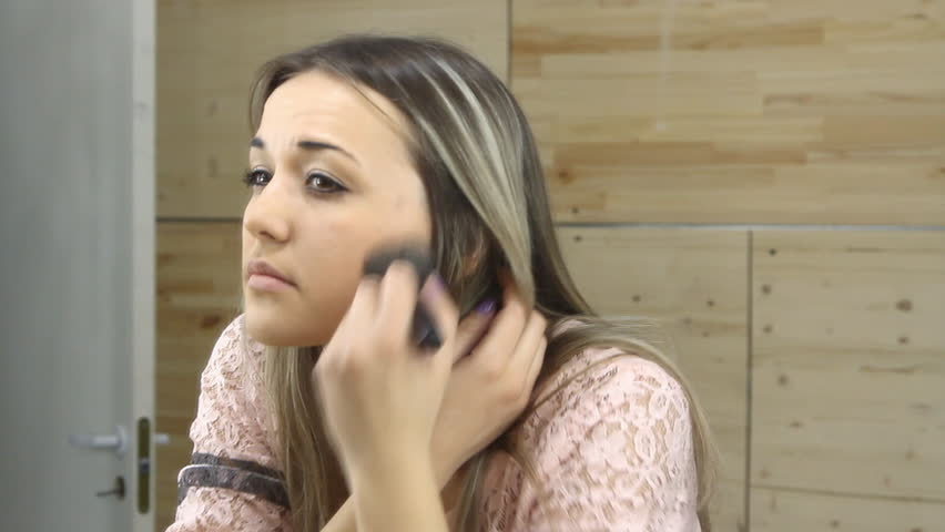 Beautiful girl looking in the mirror and applying cosmetic with a big brush | Shutterstock HD Video #9817181