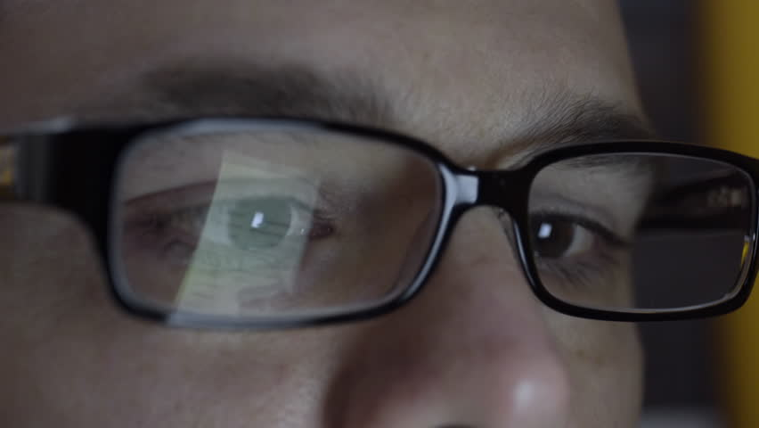 Close up of man's eye's and glasses. A reflection of him typing on a smart phone is seen. Filmed in 4K UHD. #9821147