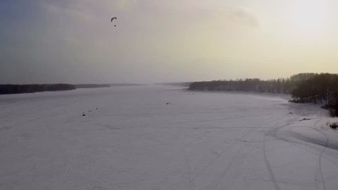 Man flies on parachute with engine above snowbound river Istra with fishers at winter evening. Aerial view