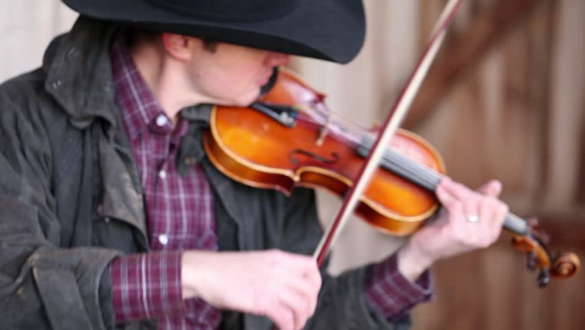 A cowboy playing the fiddle in an old barn on some haystacks for a barn dance    Shutterstock HD Video #9858134