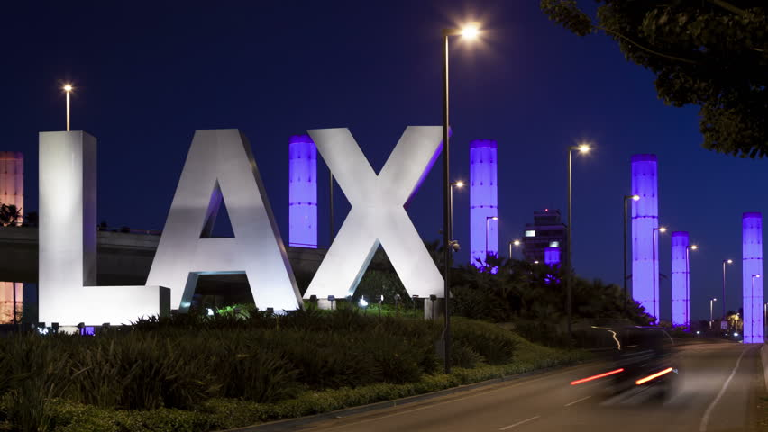 LOS ANGELES, CA, USA - APR 15, 2015: 4K Time lapse of LAX Sign at Los Angeles airport at twilight with traffic light trails