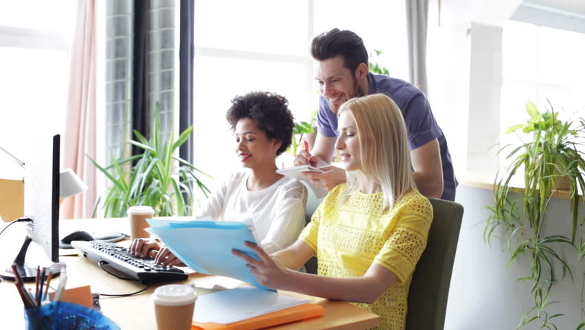 Business, startup and people concept - happy creative team with computers and folder discussing project in office   Shutterstock HD Video #9870806