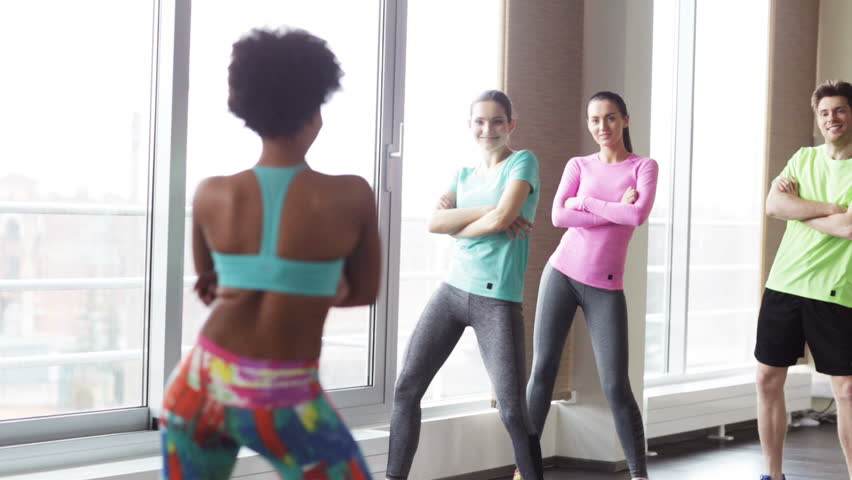 fitness, sport, dance and lifestyle concept - group of smiling people with coach dancing zumba in gym or studio Royalty-Free Stock Footage #9870824
