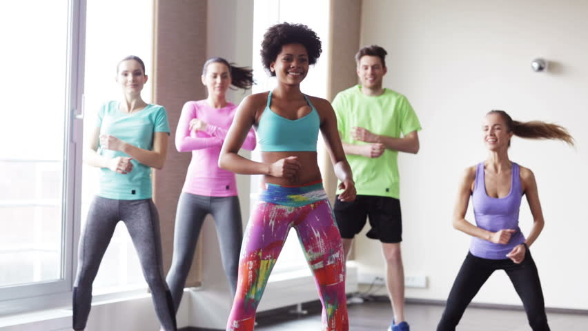 fitness, sport, dance and lifestyle concept - group of smiling people with coach dancing zumba in gym or studio Royalty-Free Stock Footage #9870851
