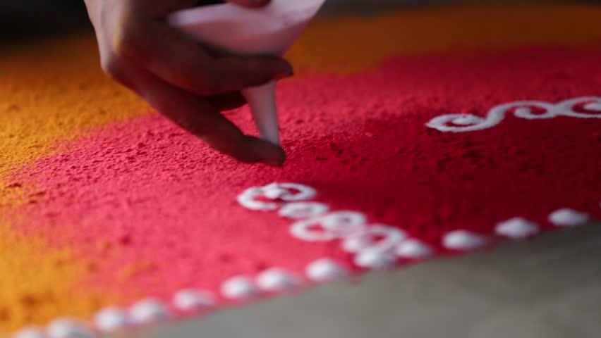 Rangoli with coloured powder being created by Rangoli artist on occasion of Hindu Wedding, Mumbai, Maharashtra, India. #9893531