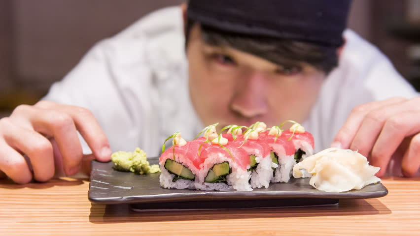 That would be tasty rolls. Selective focus on ready tasty sushi rolls standing on wooden table near concentrated Asian chef turning plate with it standing on background
