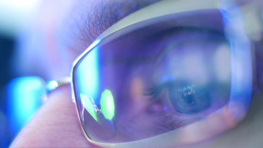 Reflection in the eye and glasses of the monitor screen when watching a movie. Close up. Shallow depth of field #9940304