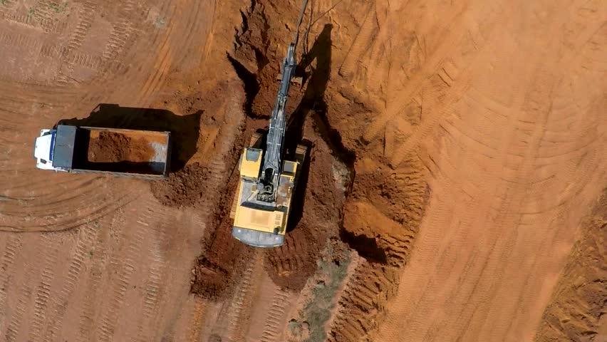 excavator scoop loads a dump truck