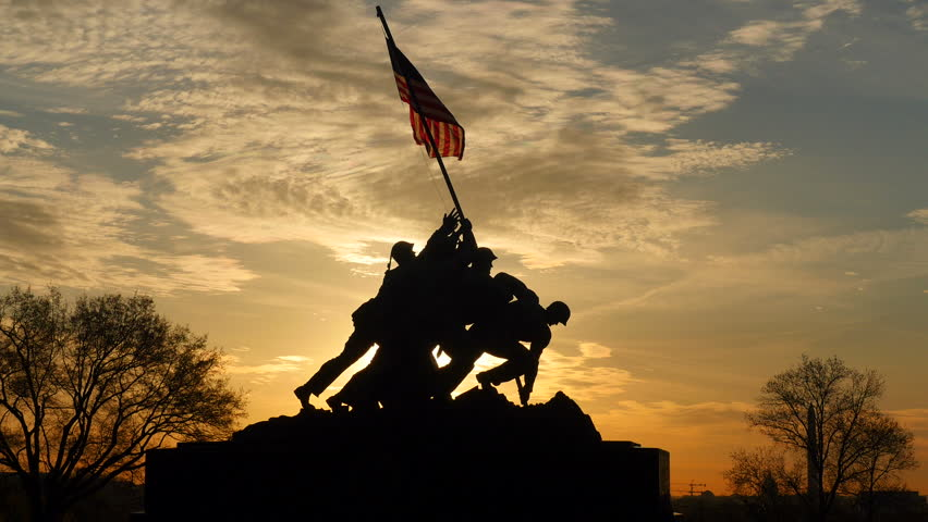 ARLINGTON, VA - APRIL 15: The Marine Corps War Memorial is silhouetted against an orange colored sky at sunrise on April 15, 2015 in Arlington, Virginia.