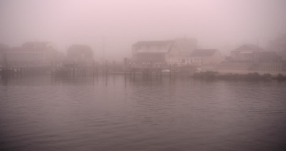 New England fishing village harbor in gloomy fog.  Water flowing and seagulls flying.
