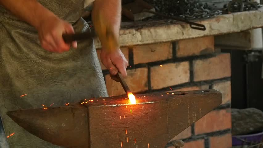 blacksmith has an effort on glowing hot metal and sparks fly in all directions, slow motion 4