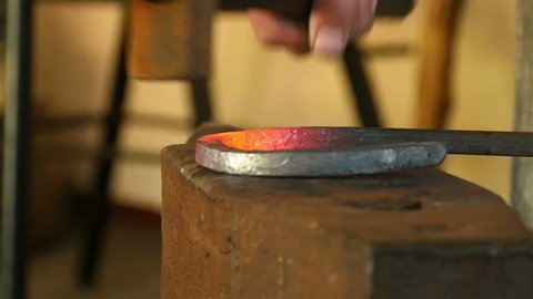 blacksmith forges a horseshoe in the workshop, closeup, slow motion 5