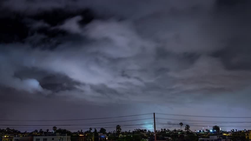Storm clouds with lightning strike bolts passing over night city of Los Angeles cityscape. 4K UHD Timelapse.